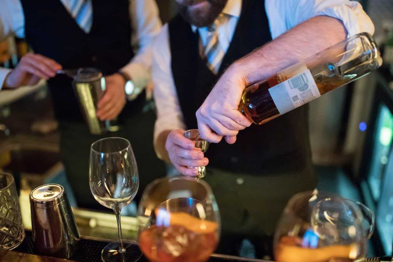 A bartender mixing a cocktails with bitters for a spirits tasting class