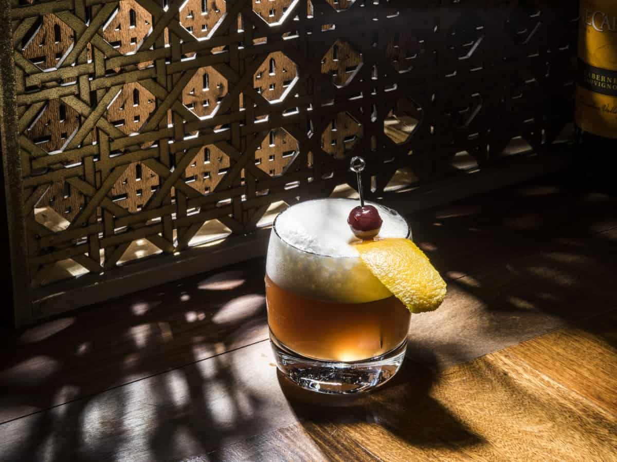 A whiskey sour by a window frame